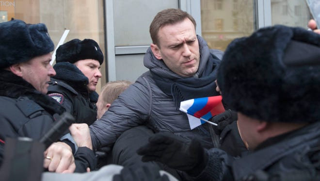 Russian opposition leader Alexei Navalny, center, is detained by police officers in Moscow on Jan. 28, 2018.