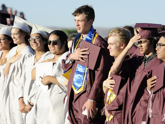 Gabriel Dums holds his cap over his heart during the