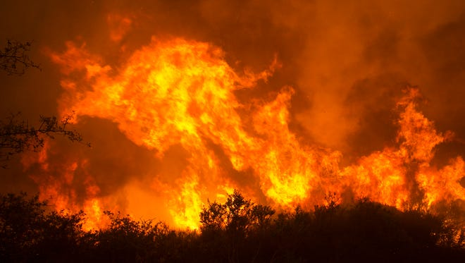 Flames from a wildfire burn Monday, Oct. 9, 2017, in Napa, Calif. The fire is one of several burning across Northern California's wine country. (AP Photo/Rich Pedroncelli)