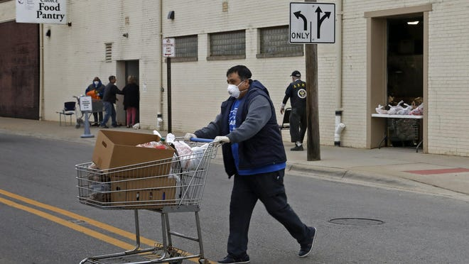 Procopio Solorzano who renently lost his job in demolition heads back to his car after he picked up food at the side door of the Lutheran Social Services food bank in Columbus on March 31. The food bank has moved to a outdoor pickup as a precaution due to coronavirus.