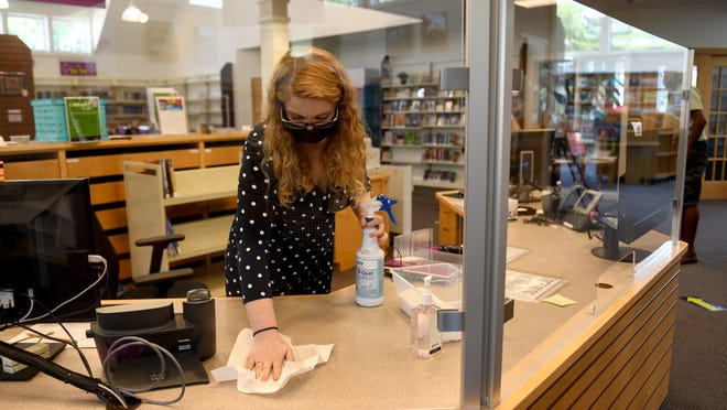 Marisha Sullivan, a youth librarian, wipes down the front desk as Stark Library DeHoff Memorial Branch, which reopened Monday with new safety guidelines.