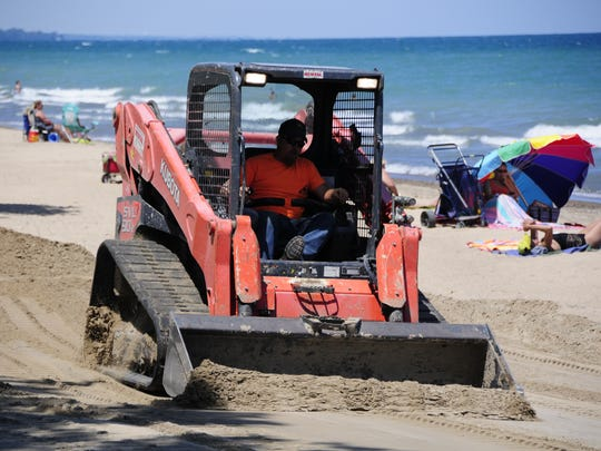 Alan Briolat uses a skid loader to groom the beach at Fort Gratiot County Park. About 500 tons of sand used during Blue Water Sandfest are being used to restore the beach.