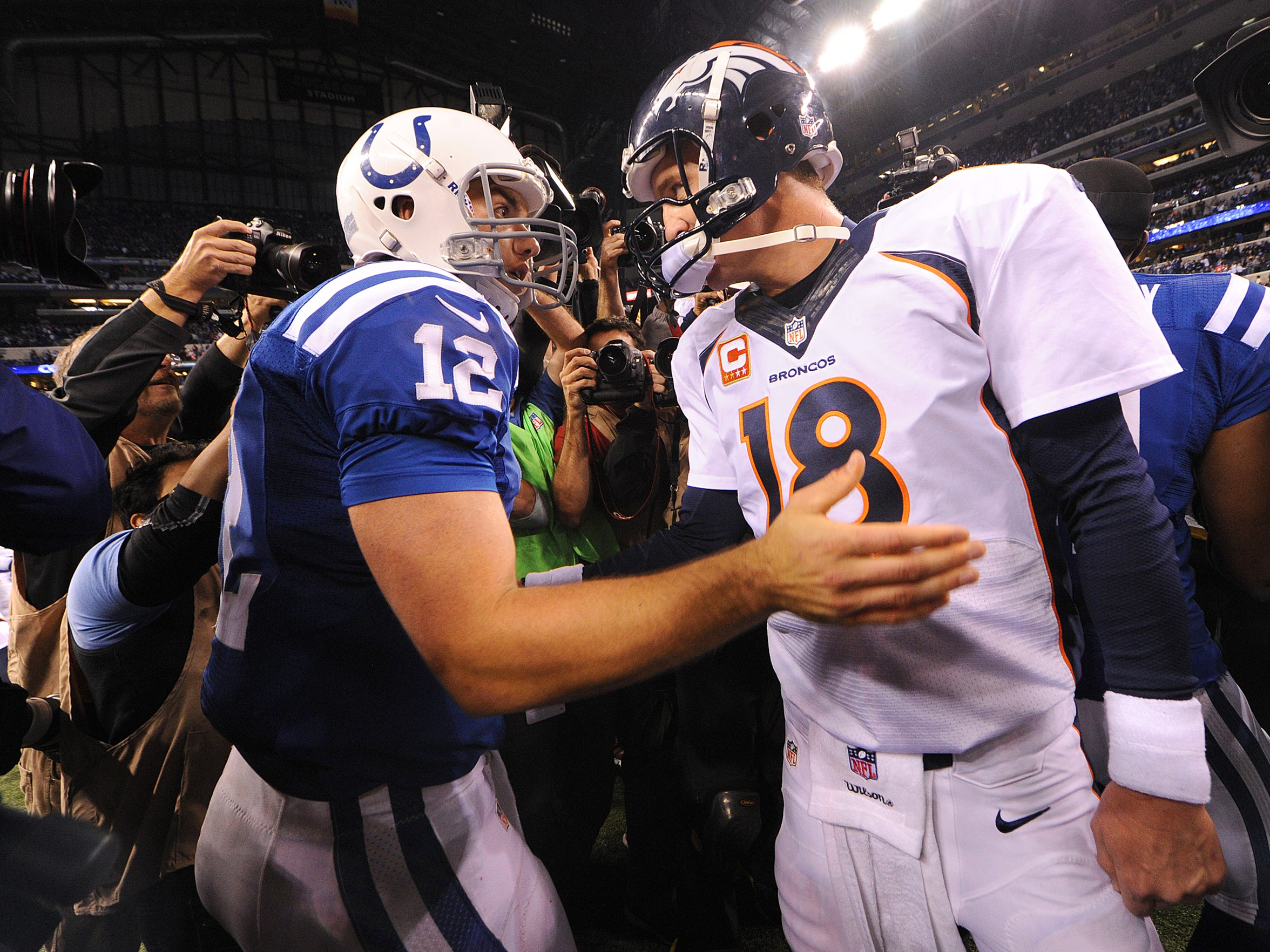 Andrew Luck and Peyton Manning meet on the field at Lucas Oil Stadium after their first NFL meeting, a 39-33 Colts win in 2013.