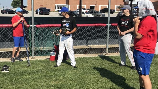 Truman baseball coach Corey Lathrom, left, visits with his players before taking the field for practice this week. Truman, William Chrisman and Van Horn high schools will play doubleheaders at each Independence high school in late June.