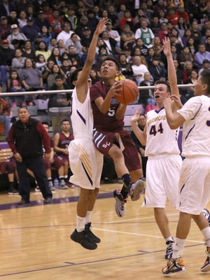 Shiprock's Elijah Harry tries a reverse layup against Kirtland Central's Ty Yellowman, left, Bryson Dowdy (44) and Bernel Miller Thursday at Bronco Arena in Kirtland.