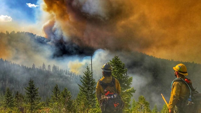 Firefighters assess the Sunrise fire, which is threatening homes southeast of western Montana's Superior.
