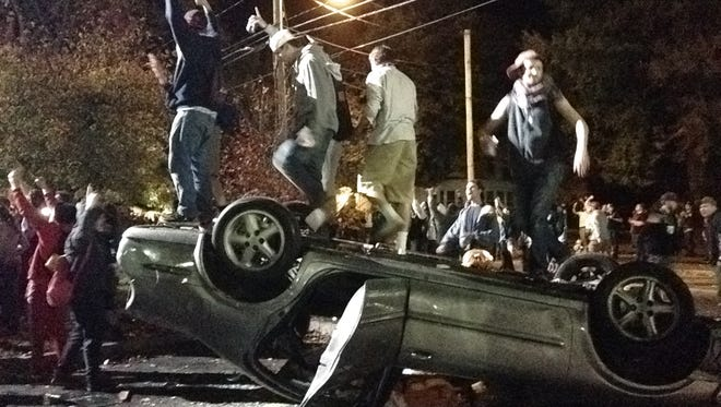 People stand atop an overturned car in Keene, N.H. on Saturday, Oct. 18, 2014, during a night of violent parties that led to destruction, dozens of arrests and multiple injuries, near the city's annual pumpkin festival. The parties around the school coincided with the annual Keene Pumpkin Festival, where the community tries to set a world record of the largest number of carved and lighted jack-o-lanterns in one place.
