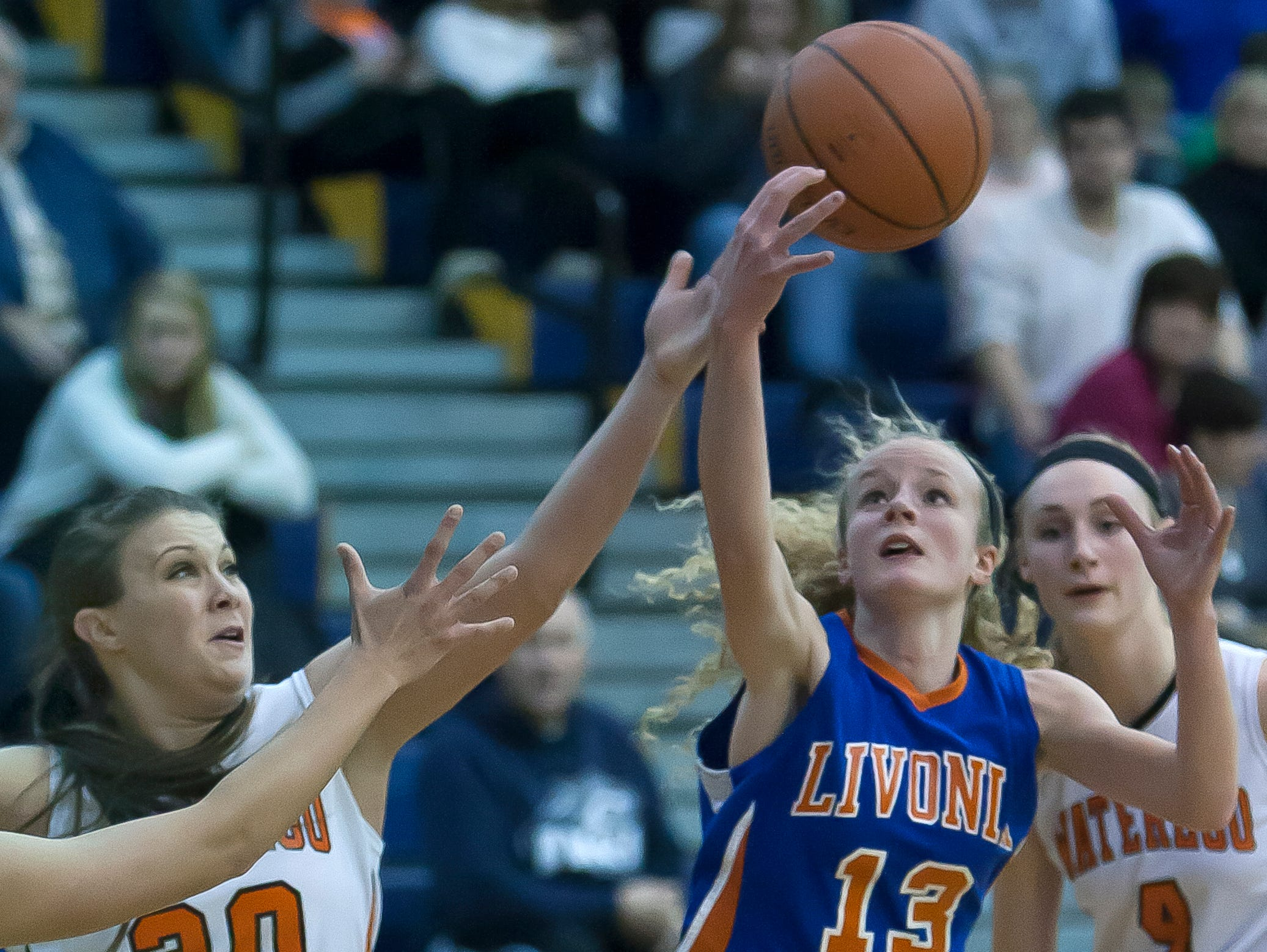 Waterloo's Chelsea France and Livonia's Molly Stewart reach for a loose ball during a game last season.