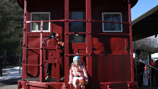 Mario and Madison Laudieri of Glenville, Connecticut play on the caboose at the Hudson Valley Rail Trail Winterfest in Highland on Saturday Jan. 13, 2018.