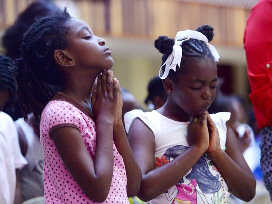 Zatara John, 7, left, and Zawadi Webber, 6, pray at Restoration Church in Antigua November 7, 2017. The two were displaced from their home in Barbuda after Hurricane Irma.