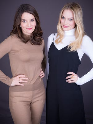 'Whiskey Tango Foxtrot' stars Tina Fey (left) and Margot Robbie pose together Feb. 19, 2016, in New York. The wartime dramedy is in theaters Friday.