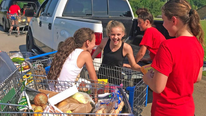 Community volunteers help load grocery items at the GraceWorks Mobile Food Pantry in Fairview on June 16, 2018.