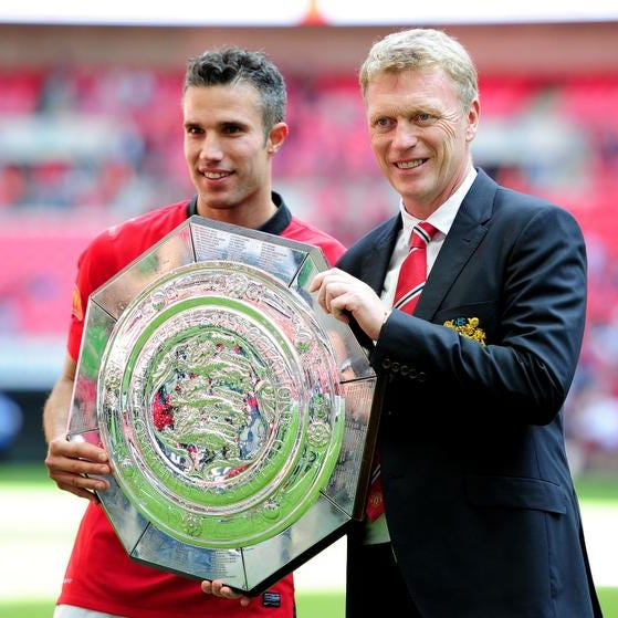 Robin van Persie of Manchester United and manager David Moyes pose with the trophy after victory in the FA Community Shield match between Manchester United and Wigan Athletic at Wembley Stadium on August 11, 2013 in London, England.