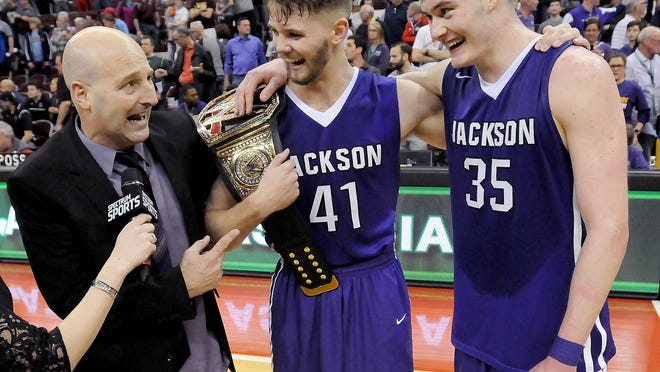 Jackson head coach Tim Debevec celebrates the state championship with Logan Hill (41) and Kyle Young (35), March 25, 2017.