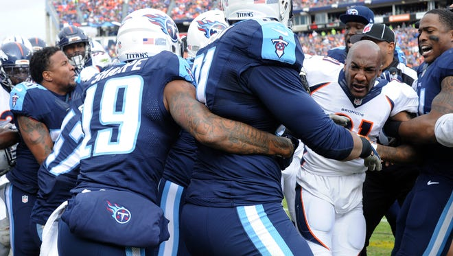 Broncos cornerback Aqib Talib (21) is peeled away from a bench-clearing brawl that started with a low block by Titans wide receiver Harry Douglas (83) in the second quarter Sunday.