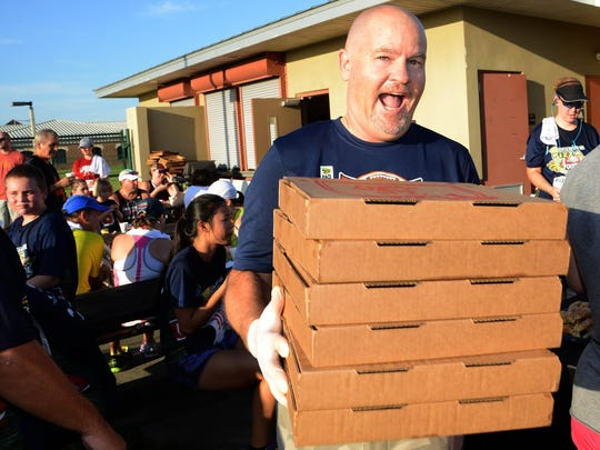 Chris Conneen of Pizza Gallery brings out more pizzas during the 2014 I Run for Pizza Football Kickoff 5K.