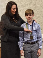 Amanda Kopp gives Caleb White receives the Virtue, Values and Vision Award from National Catholic Educational Association on Jan. 31. The Catholic Central High School freshman has been helping homeless people since he was 6.