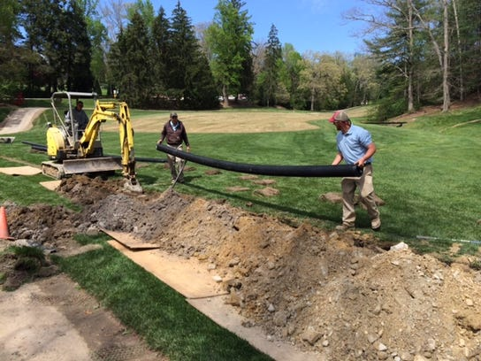 Biltmore Forest Country Club workers Roy Clark, left, and Shane Robinson, right, set a drain pipe at Biltmore Forest Country Club in 2015.