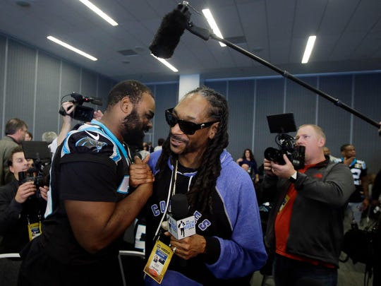 Recording artist Snoop Dogg, center, shakes hands with