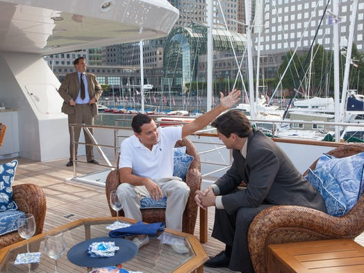 """Kyle Chandler, seated left, says his scenes alongside Leonardo DiCaprio (as Jordan Belfort in """"The Wolf of Wall Street"""") were daunting improvisational moments on his first day of shooting."""