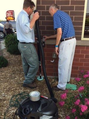 United FCS appraiser Peter Hannan, left, and home loan officer Mark Derfus use a vacuum Thursday to suction ducklings out of a downspout drain at their building in Marshfield. They rescued seven ducklings that had fallen into two drains.