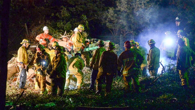 Los Angeles County Fire Dept. firefighters work at the scene where a large tree fell on a wedding party in Whittier, Calif., Dec. 17.