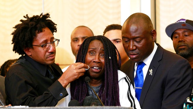 As Sequita Thompson, center, discusses the shooting of her grandson, Stephon Clark, Clark's brother, Ste' vonte Clark wipes a tear from her cheek during a news conference, Monday, March 26, 2018, in Sacramento, Calif. Clark, who was unarmed, was shot and killed by Sacramento police officers a week ago who were responding to a call about a person smashing car windows. At right is attorney Ben Crump.