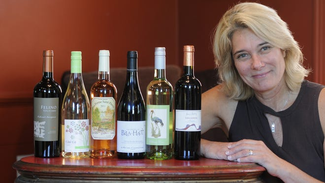Paula Young, former owner of Paula's Stone Cottage Wine Bar in Fishkill, poses with a few bottles of wine.