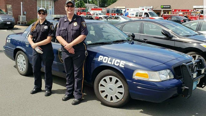 Former Interim Police Chief Roberta Sarnacki and Officer Krysten Scapin stand in front of a police cruiser. The entire Blandford Police Department quit due to unsafe working conditions.