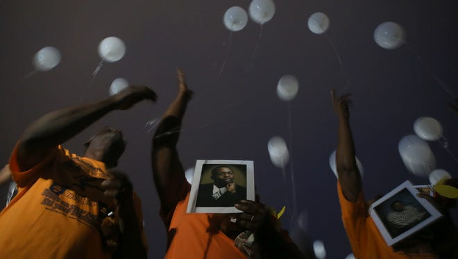Holding a photo of Jerome Ellington, Martha Epperson and other church members release balloons at the end of Remember Me Commemorative Walk at Union University on Monday night.