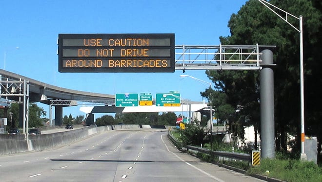 An overhead sign along on Interstate 26 warns motorists not to drive around barricades blocking storm water on area streets near Charleston.