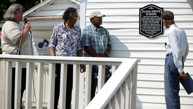 West Tennessee Delta Heritage Museaum Director Sonia Outlaw-Clark reads the historical plaque for the Flagg Grove School, Saturday during Tina Turner Heritage Days. Clark is joined with the grandchildren of Flagg, Darnisha Halliburton, Kent Flagg, and McCauley Flagg.