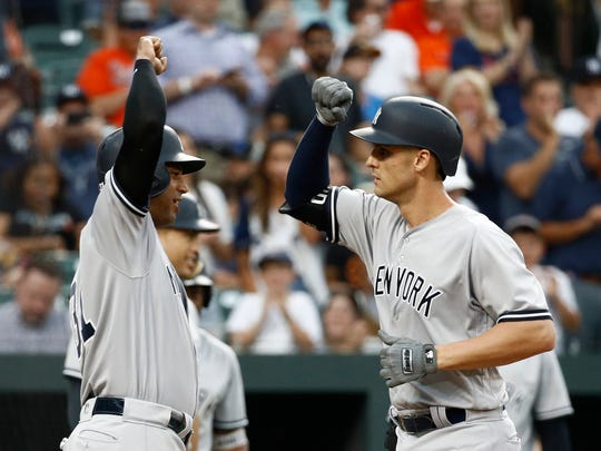 New York Yankees' Aaron Hicks, left, greets teammate Greg Bird after scoring on Bird's grand slam in the third inning of a baseball game against the Baltimore Orioles, Wednesday, July 11, 2018, in Baltimore.