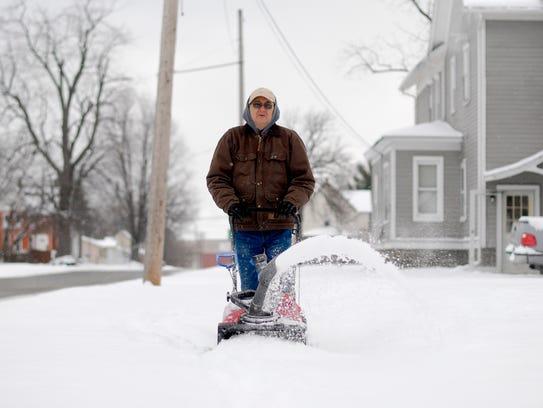 Bob Tremble takes his snowblower to the sidewalk Monday,