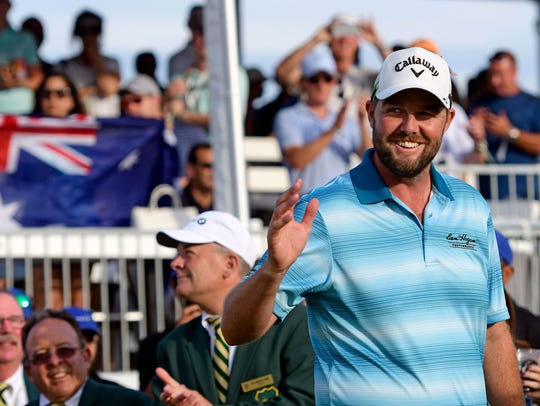 Marc Leishman walks on the 18th green  to receive his