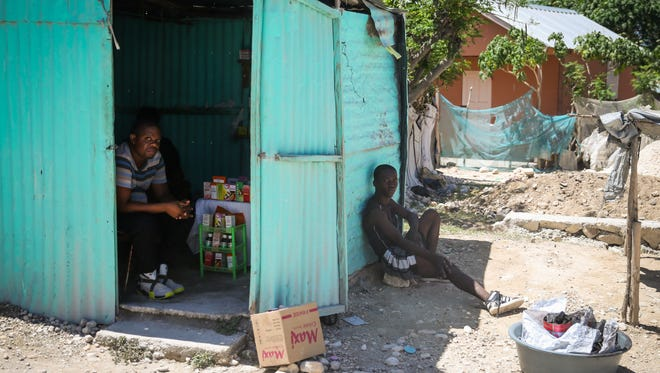 Men sit in the shade with items for sale in Onaville. Many residents of the refugee city depend on the sale of odds and ends to live.