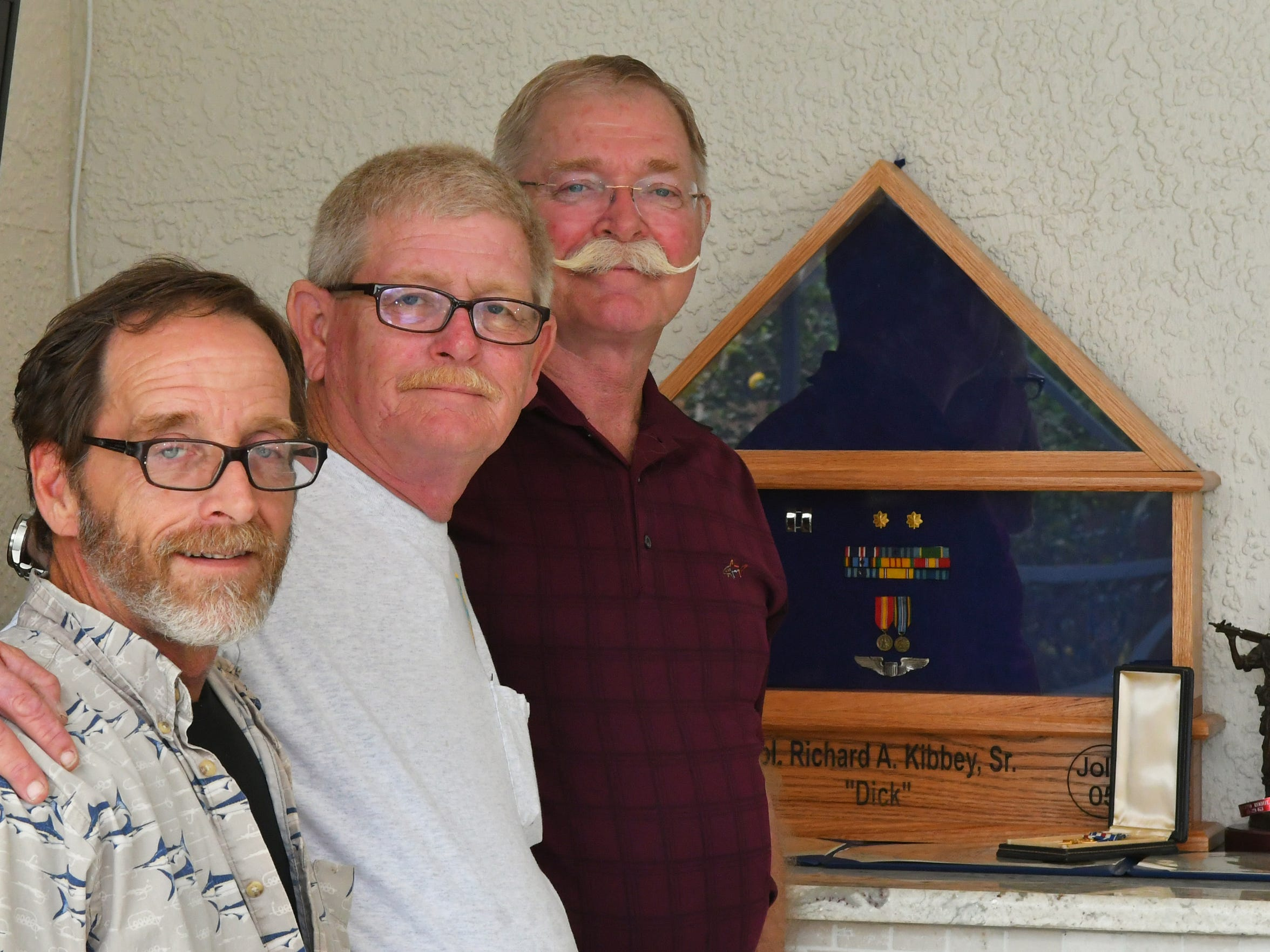 Col. Richard Kibbey's sons (left to right) John, 52, Dave, 58, and Rick, 63, stand by the modified flag box that will house their father's dog tags at Rick Kibbey's Viera home. Dave Kibbey built the oak flag box.