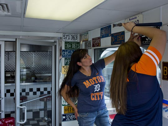 Toni Braley, of Port Huron, and Nichole Symes-Hoskins, of St. Clair, hang up vintage license plates on a wall Thursday, June 25, 2015 at Powers Diner in Port Huron. The Diner will be having a soft opening Friday through Sunday.
