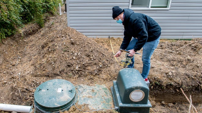 Tazewell County environmental health specialist Bruce Johnson takes measurements during an inspection of a new residential septic system on Tuesday in Groveland.