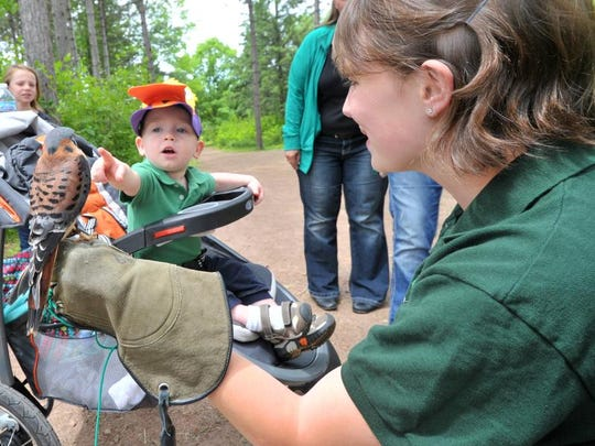 One-year-old Brady Baumann of Mosinee points to a raptor held by Nicole Hildebrandt, an intern at REGI, Saturday at the Robert W. Monk Public Gardens in Wausau. The raptors are provided by the Raptor Education Group Inc. in Antigo.