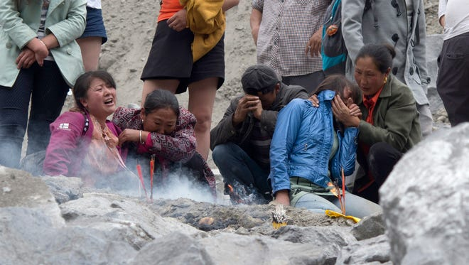 Rescue workers wait as heavy machinery clears dirt at the site of a landslide in Xinmo village in Maoxian County in southwestern China's Sichuan Province on Sunday, June 25, 2017.