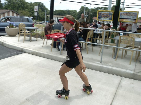 Carhop and trainer Rachael Coker skates off after delivering food to customers at the newly-opened Sonic restaurant on Upper Front Street in July, 2009