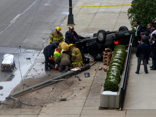 Firefighters free the driver of a car that flipped over and hits the steps of the Fort Street entrance of the federal courthouse in downtown Detroit.