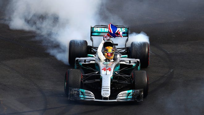 Lewis Hamilton celebrates with a burnout after winning his fourth Formula One championship Sunday at the Mexican Grand Prix.