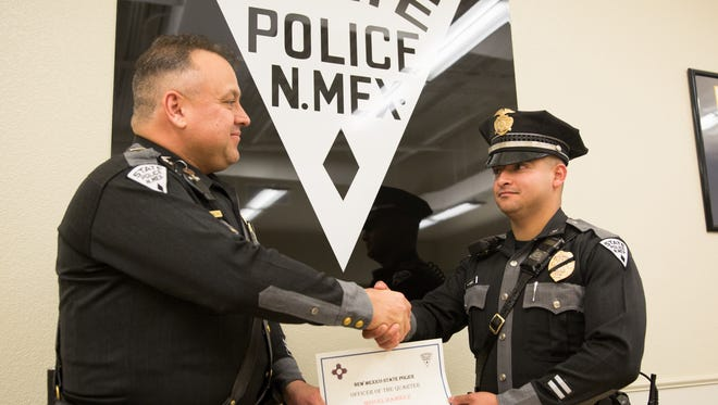 """New Mexico State Police Officer Miguel Ramirez, right, of Las Cruces, is presented the Officer of the Quarter award on July 25, 2016, by Lt. Ramon Terrazas. Ramirez has been with the Las Cruces district for less than a year, but has """"made a big impact"""" during that time, according to Terrazas. Between April and June, Ramirez issued 357 citations, made 24 arrests, and assisted in six crashes and nine cases. The award is handed each quarter in the Las Cruces district. The officers who receive the award are also eligible for consideration to be picked as New Mexico State Police officer of the year."""