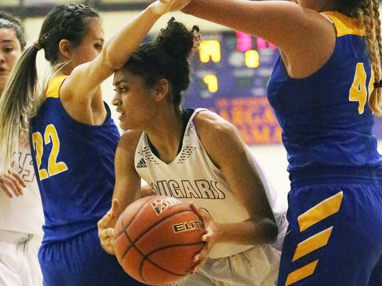 Cierra Winters, center, of Franklin looks for an outlet while being boxed in by Kaylee Martinez, left, and Alexa Hidalgo of Eastwood Friday night at Franklin. The Cougars topped the Troopers 33-29.