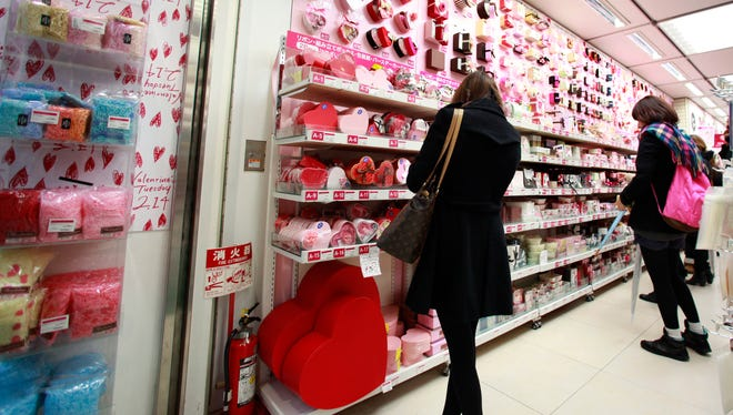 FILE - In this Feb. 14, 2012 file photo, women look at heart-shaped boxes containing Valentine's Day chocolates on sale at a store in Tokyo. In Japan, women buy chocolates for men on Valentine's Day, not vice versa. And not just for their boyfriend or partner, but also for co-workers, friends of both sexes and even themselves these days.  (AP Photo/Shizuo Kambayashi, File)