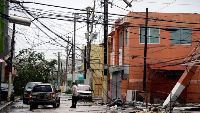 Power lines are down Sept. 20, 2017, after Hurricane Maria, which hit the eastern region of the island in Humacao, Puerto Rico. Experts say rebuilding an above-ground wired electric grid isn't the best way to proceed.