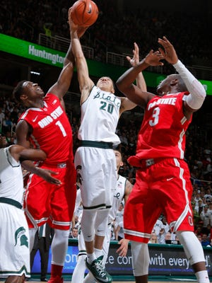 Michigan State's Travis Trice (20) and Ohio State's Jae'Sean Tate (1) and Shannon Scott (3) reach for a rebound during the first half Saturday in East Lansing.