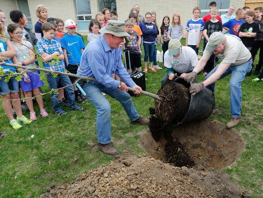 Mintonye Elementary School fifth grade students look on as Greg Shaner, from left, Don Schreiber and John Slaven of Tree Lafayette prepare a tulip tree for planting Monday, April 21, 2014, at Mintonye Elementary School. Mintonye fifth graders joined Tree Lafayette in planting the tree at their school, which was severely damaged last November by a tornado. Mintonye Principal Rob Skaggs said the tree is dedicated to the fifth grade class as they will not be returning to Mintonye next fall when repairs to the building are completed and classes resume.